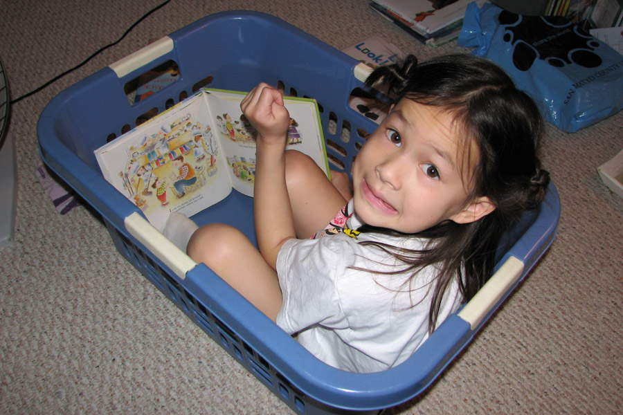 Cookies & Clogs | Everything changes when you have kids. Parenthood makes you do and say things you never thought you'd do when raising children. See how our parenting experience has gone and what two things have helped with cleaning up their messes. Child in laundry basket reading with mischievous expression.