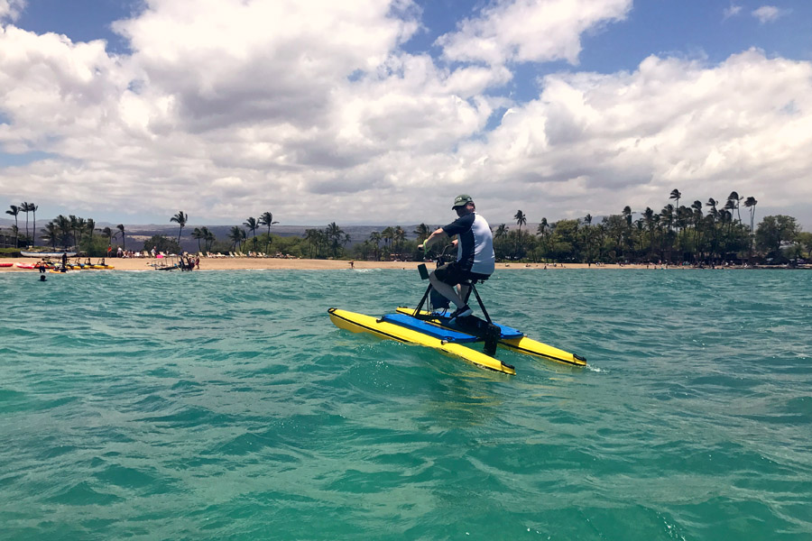 Cookies & Clogs | Oceans Sports Aloha Days offer 4 hours of unlimited water sports beach equipment including kayaks, stand-up paddleboards, snorkel gear, and rides on the glass bottom boat. One of the many things to do on the Big Island of Hawaii with kids. Man on hydro bike.