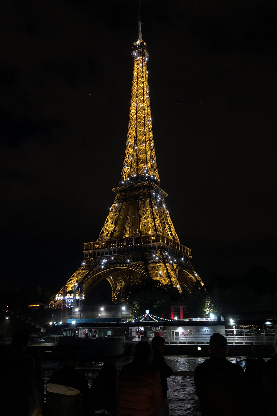 Best Paris boat tour tips for sightseeing cruise on the Seine River in Paris, France. Eiffel tower at night sparkling